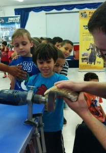 Children in Acre line up to help transform a ram's horn into a shofar