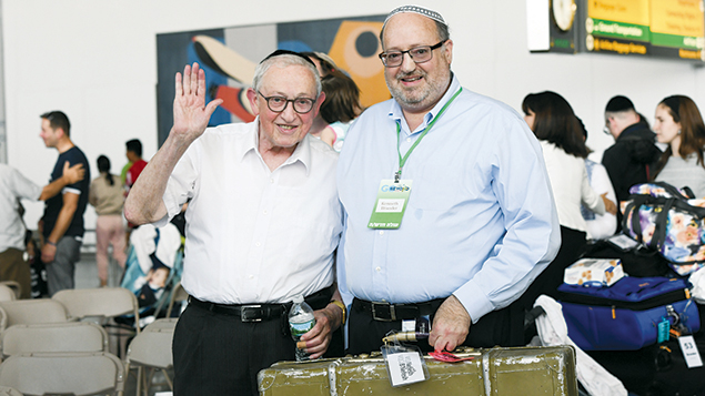 Rabbi Aaron Brander hands the suitcase he carried out of Europe to his son, Rabbi Kenneth. (Nefesh B'Nefesh)