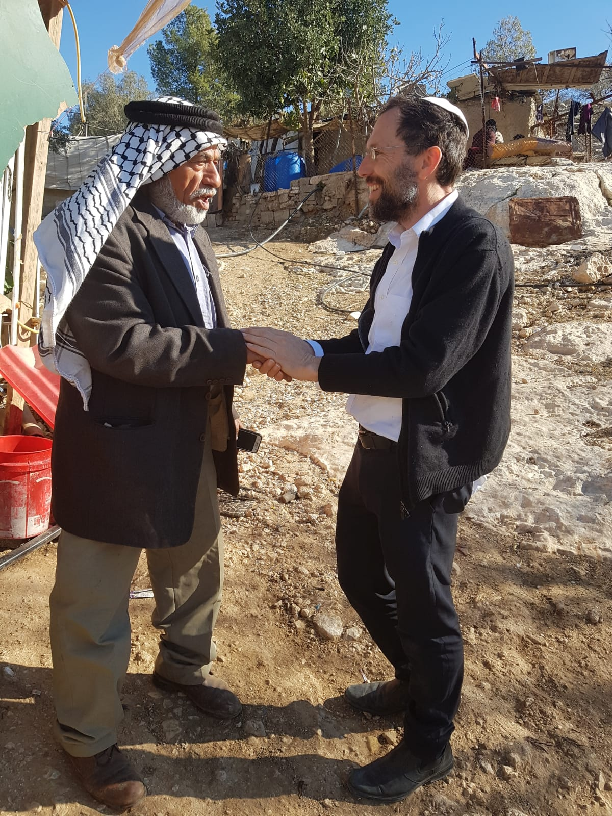 Rabbi Yakov Nagen on a visit with a neighbor in the Hebron hills