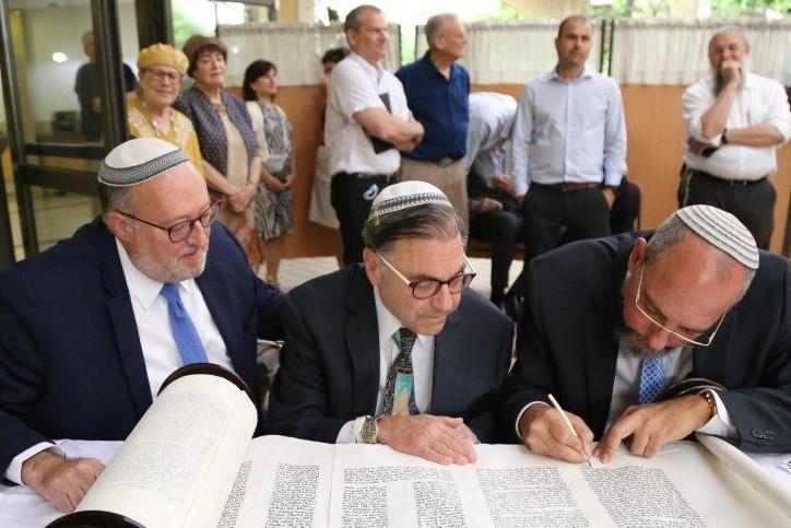 Rabbi Riskin writing a letter in the scroll